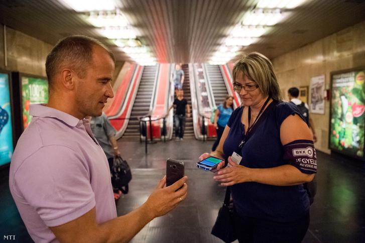 Utas új elektronikus bérletét ellenőrzi a Budapesti Közlekedési Központ (BKK) jegyellenőre Budapesten, a Deák téri metrómegállóban 2017. július 18-án.