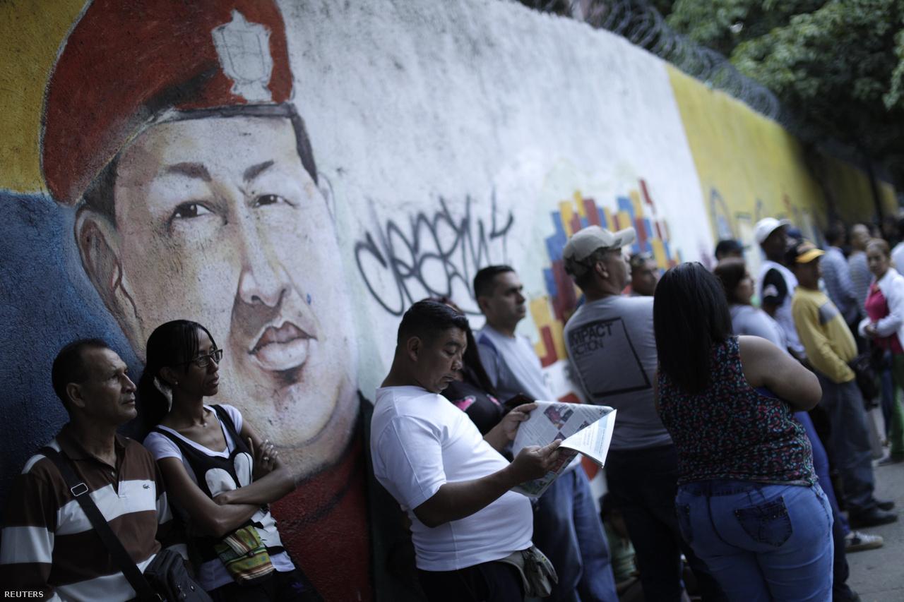 Szavazásra váró emberek Chavez falfestménye alatt.