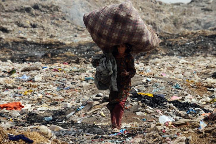 Egy nő ruhákat gyűjt a szemétből egy pakisztáni szeméttelepen