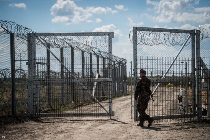 Egy katona a kaput zárja be a járőrautó behajtása után a magyar-szerb határon álló biztonsági határzáron Kübekházánál 2017. május 27-én