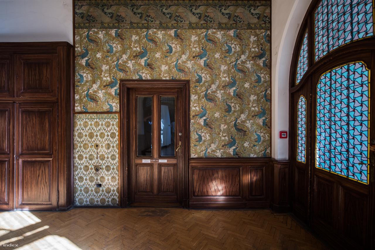 """Ezért a dizájner tapétáért epedhetett annak idején """"tout Pest"""", vagyis az egész előkelő társaság. Dr. Radisics Jenő (1856-1917), az Üllői úti palotába költözött múzeum első igazgatója a korszak egyik sztár-tervezőjétől, Walter Crane-től rendelte a Pávakert-tapétát. A szekrény az egykori ételliftet rejti, a tapétával színben harmonizáló csempéken falikút függött. A korszakban megszokott volt """"az igazgatói internátus"""" (a Pesti Napló hívta így), vagyis az igazgatóság múzeumi bentlakása. Rajta kívül a közvetlen, fizikai felügyeletet végző személyzet (a portás, a házmester és az őrök) élvezhette a múzeum és az iskola titkos éjszakai életét."""