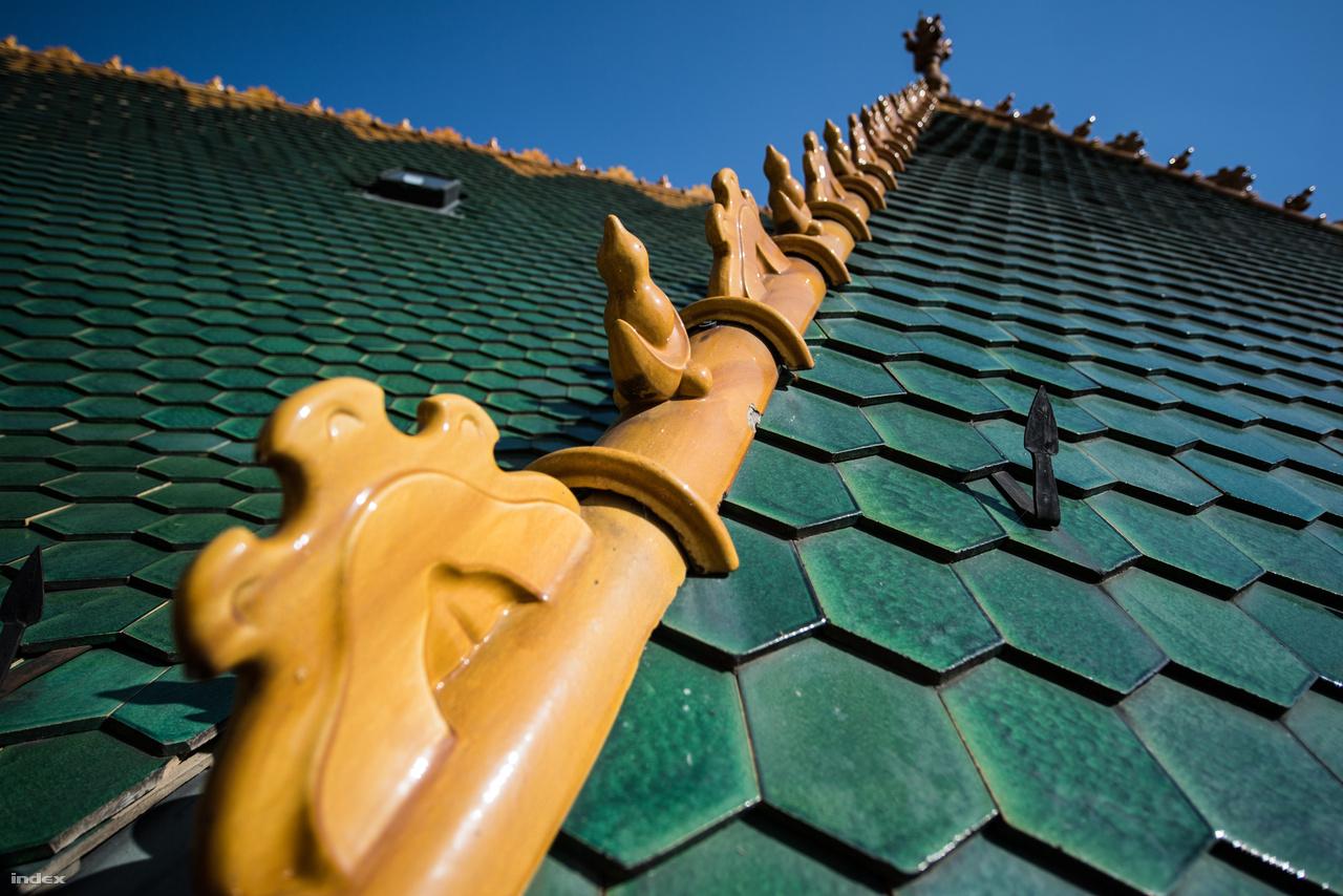 A mázas tetőcserepek sokféle zöldjéről és a tetőlezáró pirogránit díszítések sárgájáról Zsolnay, a nagy kékségről a természet gondoskodott.