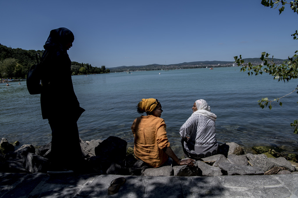 """Vagy, hogy a nők válasszák ki, hogy a strand melyik részén szeretnének leheveredni. A választás végül egy félreeső placcra esett.                         Az idősebb férfiak azonban tartózkodtak a víztől: nem akartak idegen, fürdőruhában lévő nőkkel együtt fürdeni. A csoporthoz tartozó nők közül azonban többen is bementek a vízbe. """"Minden tetszik, a víz nagyon jó"""" – mondta egyikük. Ő Budapesten is el szokott járni úszni, persze, akkor is burkiniben. Azt mondta, előfordul, hogy ilyenkor a helyiek beszólnak neki, de ezekre nem figyel oda, és sok a kedves ember is. A tihanyi strandon például nem kapott megjegyzést."""