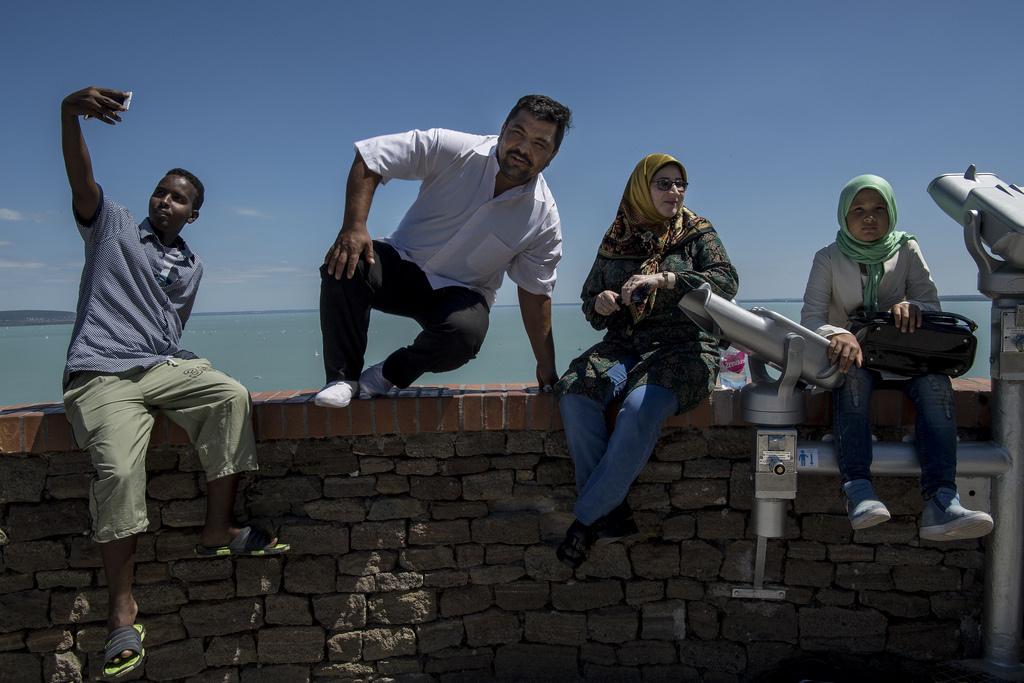 """""""Jézus Mária, kik ezek, szíriaiak?"""" – mondta egy nő, amikor meglátta a csoportot, pedig a menekülteket alig-alig lehetett megkülönböztetni bármelyik másik, éppen Tihanyban lévő turista-csoporttól: fényképezkedtek az apátsággal, a tóval, egymással."""