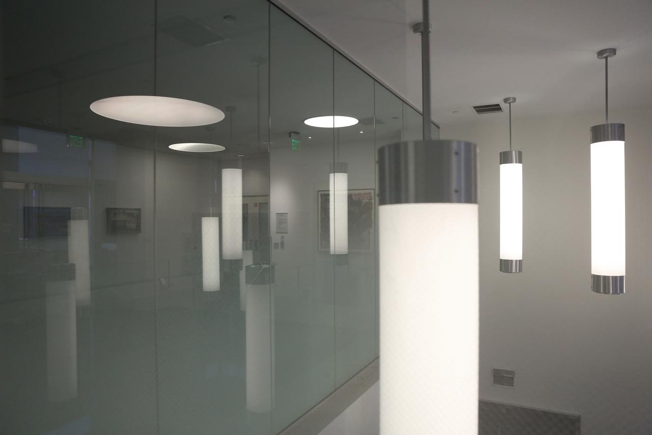 Lépcsőházi világítás, az üvegfal mögött kis képzőművészeti tárlat.