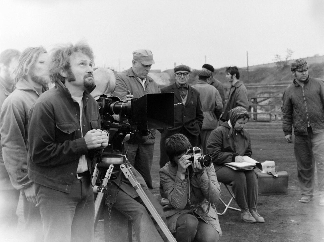 """Bal oldalt Sándor Pál rendező tekint fel az égre. """"Borúra várva, ez lehetne a kép címe, mert Ragályi azt találta ki, hogy ezt a filmet csak borúban lehet forgatni. Volt olyan, hogy kimentünk a szeméttelepre, és vártuk, hogy elmenjen a nap, hogy szép legyen a film."""" - emlékszik vissza a rendező. Sándor mellett Bánk László asszisztens sapkában, a kamera alatt B. Müller Magda, a film hivatalos fotósa fotózza a készülő jelenetet. Jávor István viszont a stábról csinált képet: """"Sándor Pálról nagyon jó portrékat lehet lőni, olyan mimikája van mint Louis de Funes-nek."""""""