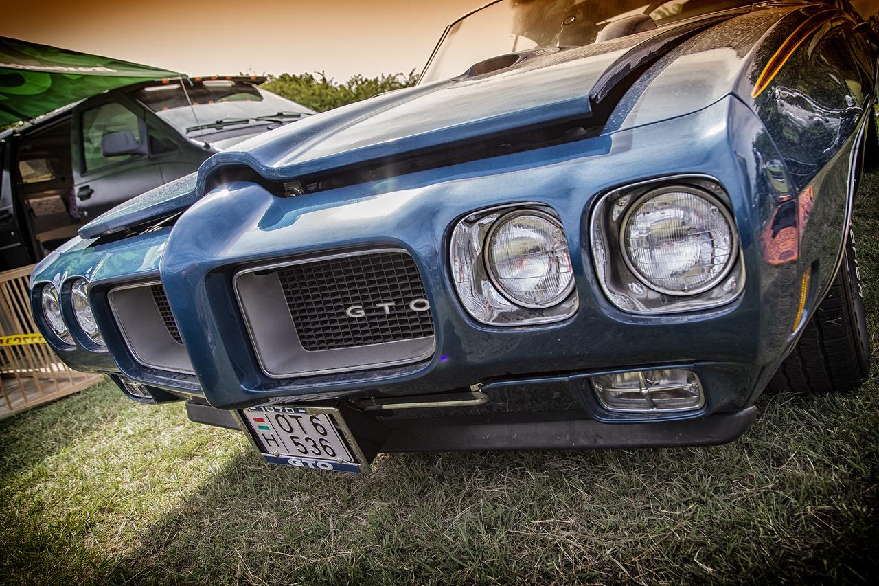 A jellegzetes, két nagy orrlyukkal fújtató Pontiac GTO 1970-ből, gyönyörű állapotban, veteránvizsgával. Igazi legendás muscle car, amelynek tervezésénél és névadásánál (Grand Tempest Option) John DeLorean is atyáskodott (igen, az a DeLorean, aki a Vissza a jövőbe című kultikus mozifilm DMC-jét is megalkotta.)
