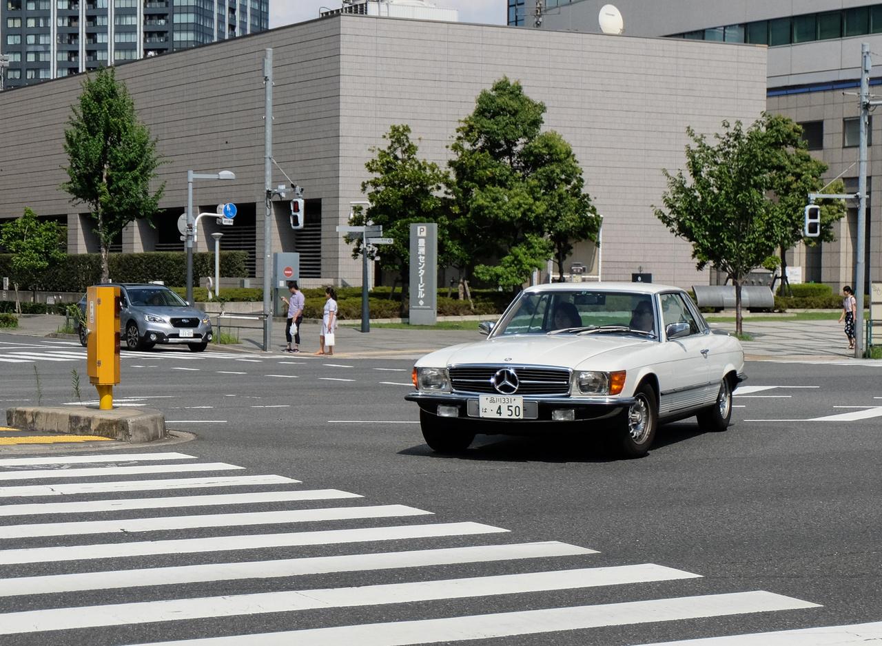 Miközben BMW-ben térdig gázol az ember, hiszen annyi van belőle, mintha a bajorok óriási gyárat létesítettek volna Japánban, a Mercedesek jelenléte kezd halványulni. De öreg Mergákból nincs hiány, itt egy SLC a hetvenes évekből az új, tengerből elhóditott nagy Tokió melletti szigeten, Odaibán