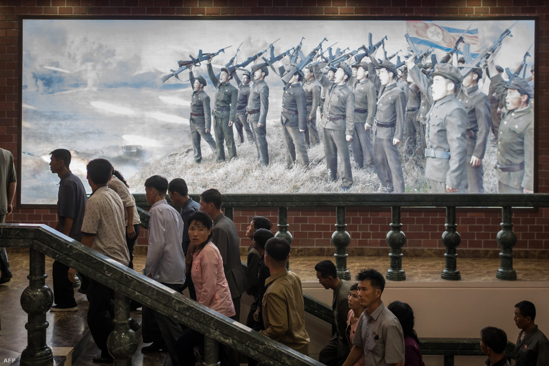 Észak-koreai metrókijárat katonai propagandaplakáttal