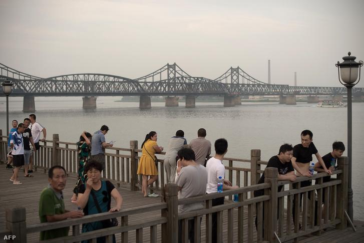 Turisták figyelik az északi oldalt a két Koreát elválasztó partvidék egyik teraszán