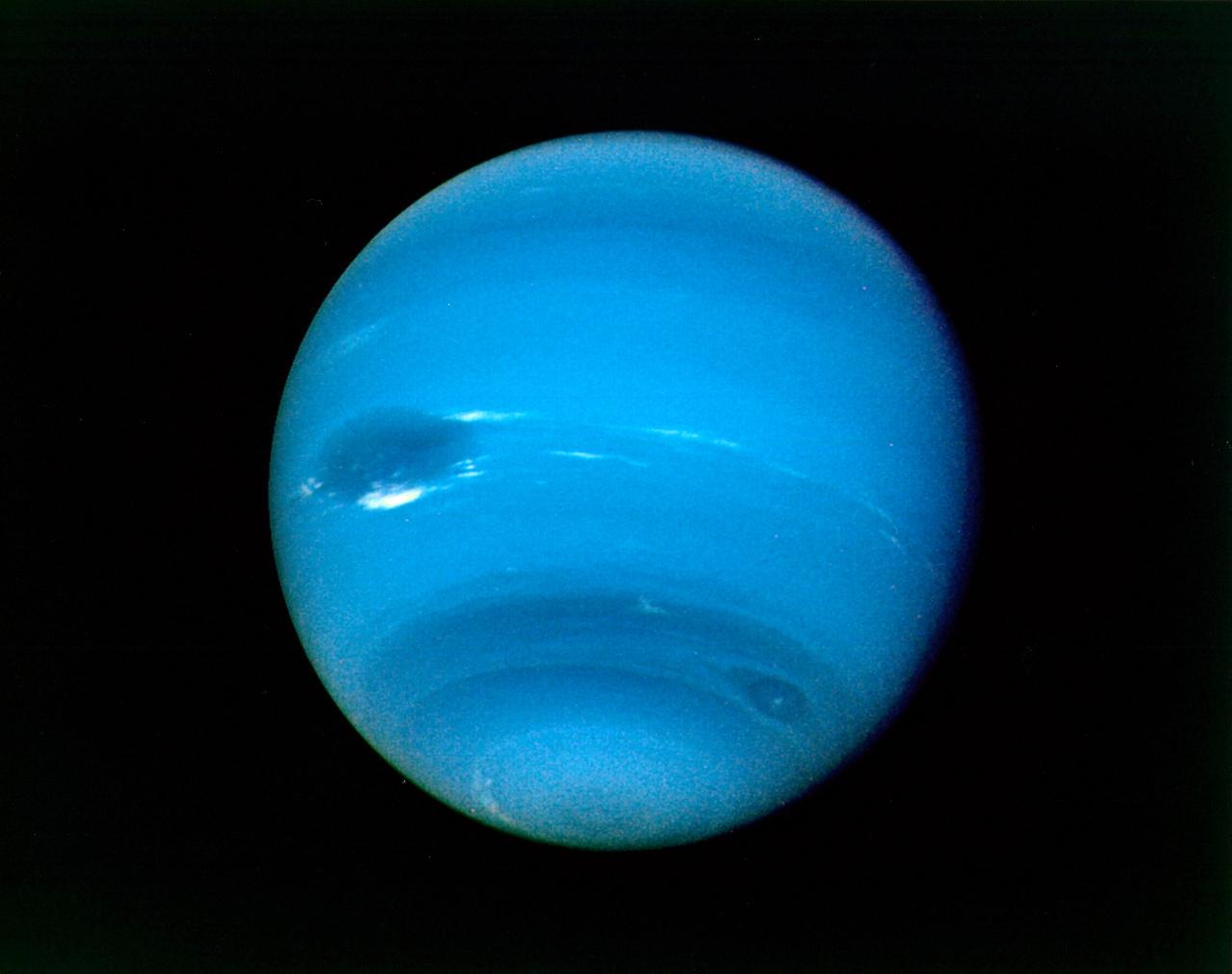 1989. augusztus 16. és 17. között. A Voyager 2 szinte folyamatosan fényképezte a Neptunuszt, ami ezen időszak alatt két és félszer fordult meg tengelye körül. A képen jól látható a bolygó egyik nevezetes nagy sötét foltja, ami a Jupiter vörös foltjához hasonlatosan egy hatalmas viharrendszer. Jobbra lent, egy kisebb jellegzetes sötét viharfolt is megfigyelhető.