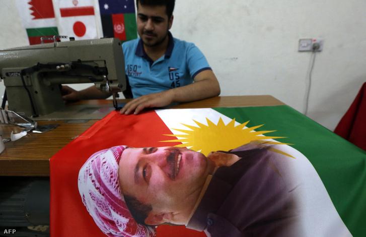 Egy férfi Maszúd Barzani arcával díszített kurd zászlót varr 2017. június 8-án