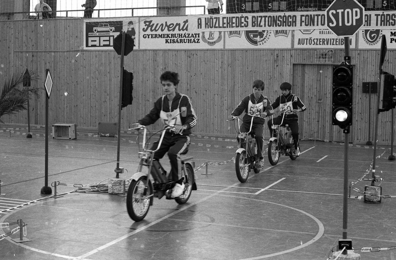 Az iskolásoknak KRESZ-vetélkedőket, ifjúsági közlekedésbiztonsági kupákat rendeztek. Ezen a képen a segéd-motorkerékpárosok szabályossági versenyének döntőjén Jawa Babettá-sok szlamoznak az egri körcsarnokban. De a Babettákig hosszú út vezetett az ötvenes évektől.
