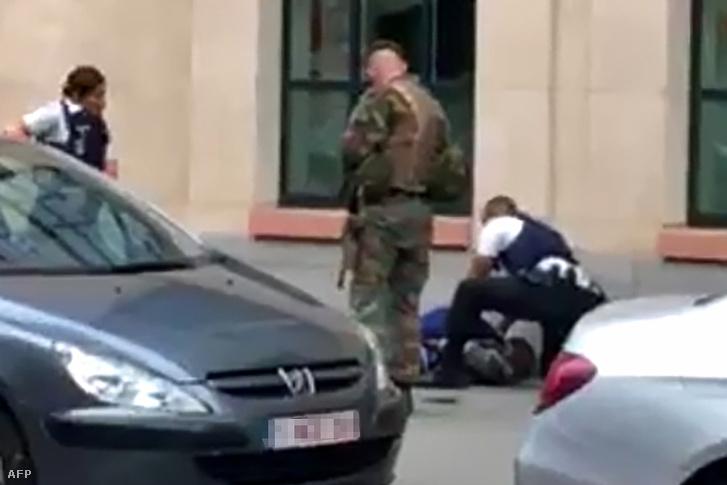 Rendőrök bilincselik meg azt a férfit, aki hátulról, egy bozótvágóval támadt két katonára Brüsszel belvárosában, 2017 augusztus 25-én.