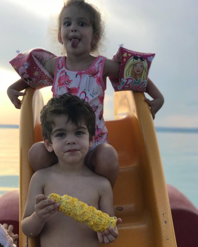 Vencel cukin eszegeti a főtt kukoricáját, míg Mici a háta mögött trollkodik.