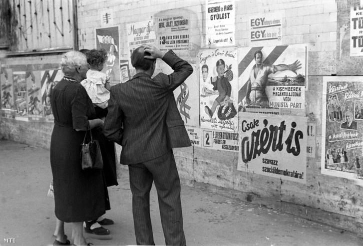 Járókelők nézik a Magyar Kommunista és a Szociáldemokrata Párt plakátjait a fővárosban