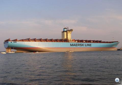 A világ egyik legnagyobb teherhajója. Baloldalt a kormánylapát mellett egy kétárbocos vitorlás.
