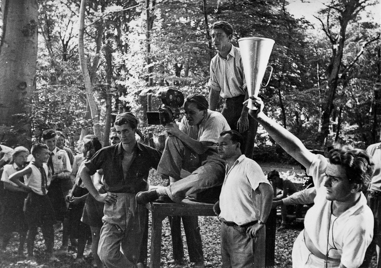 Az állványon Makk Károly figyeli a jelenetet, amit ARRI kamerával kezében Pásztor István, a fiatalon elhunyt operatőr rögzít. Tőlük balra Hildebrand István, az egyik legtehetségesebb magyar operatőr, ekkor még filmművészeti főiskolás. A film címe sajnos itt sem ismert, de nagyon valószínű, hogy az 1949-ben forgatott, majd betiltott és megsemmisített Úttörők című film forgatásán készült ez a kép.