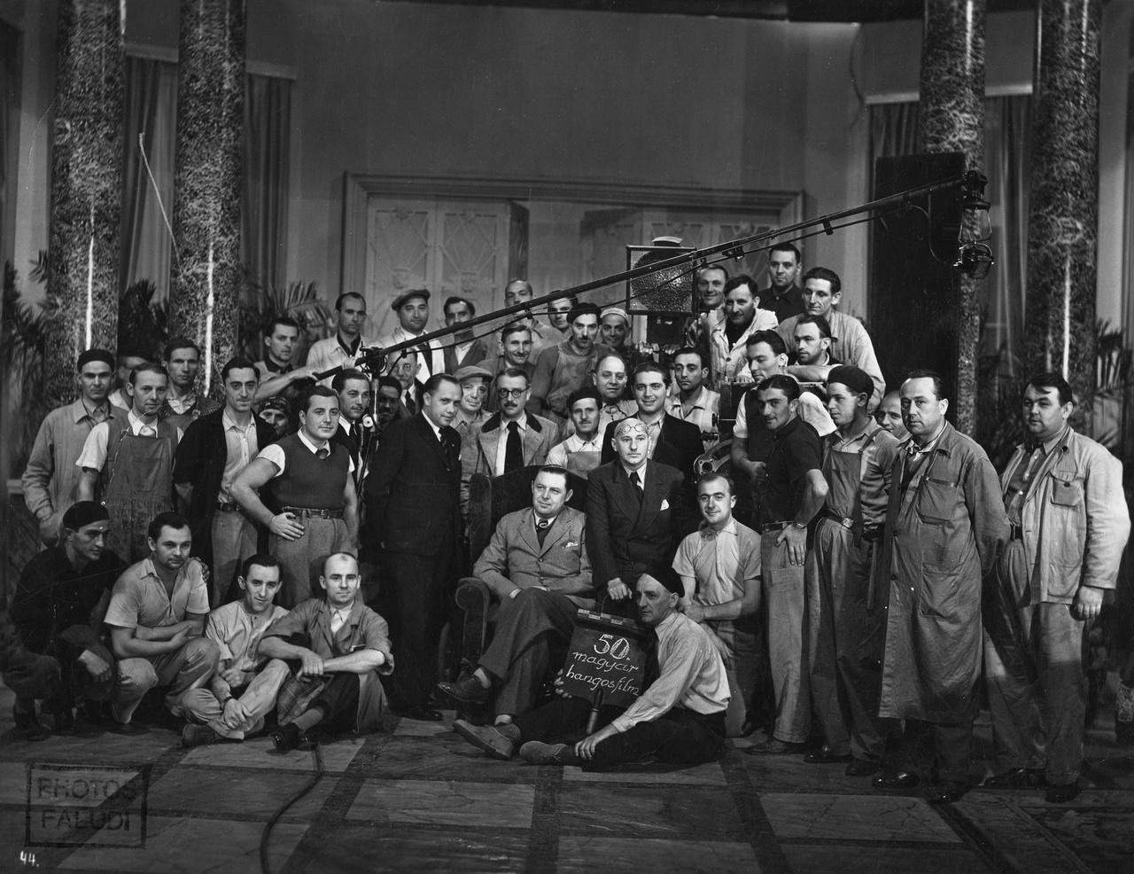 Az ötvenedik magyar hangosfilm stábfotójára még a Hunnia igazgatója, Bingert János is beült. Fotelje mellett a gyár aligazgatója, Nagy Sándor áll, a másik oldalon Balogh Béla filmrendező ül a karfán. Régi nagy némafilmrendezőnk volt, aki a hangos korszakban is sokat dolgozott. Ő rendezte ezt az 1936-os produkciót is, amelynek munkacímei hetente cserélődtek. Végül a Méltóságos kisasszony mellett kötöttek ki, és ez lett a későbbi filmcsillag, Szeleczky Zita első filmje.