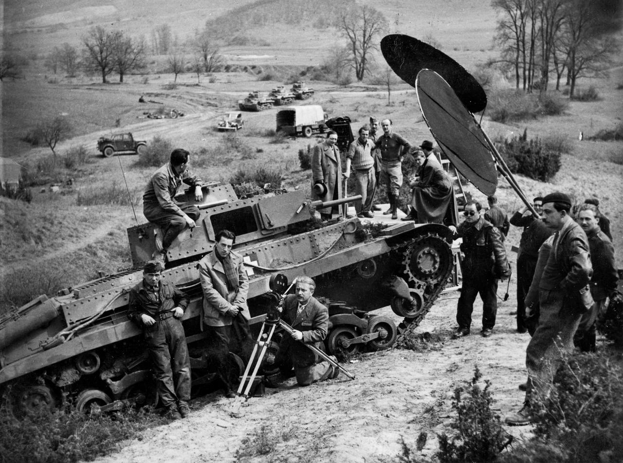 """Egy elveszett film werkfotója 1943-ból. Az Anyámasszony katonája c. háborús vígjáték a fennmaradt forgatókönyv alapján ítélve jó párbeszédekkel teleírt, színvonalas vígjáték lehetett. Külső jeleneteit a honvédség közreműködésével valahol a budai hegyekben vehették fel, a filmgyárból csak a kamerákat, a hangosztályt és két """"négert"""", azaz fénytakaró maszkot mozgósítottak."""
