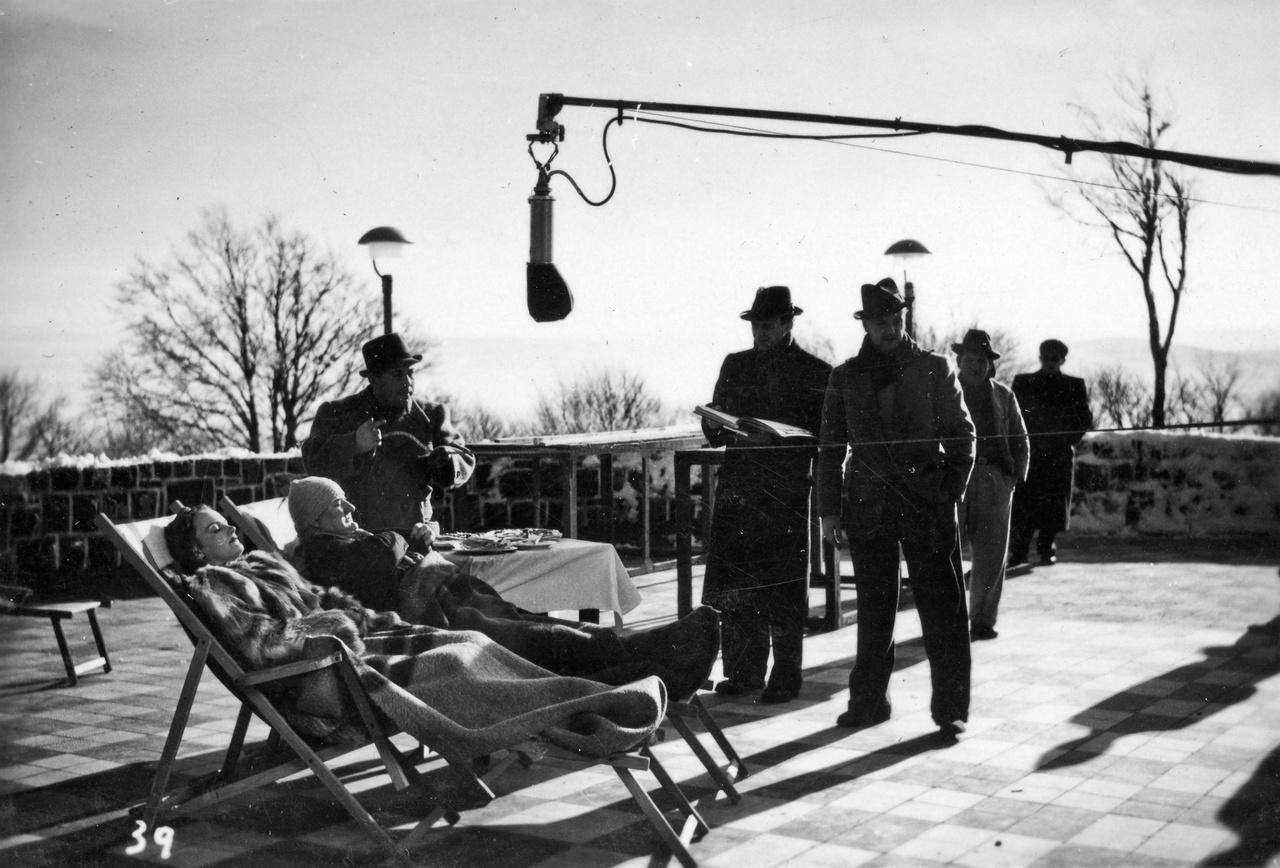 A külső felvételek azonban olykor mégis elkerülhetetlenek voltak, főleg ha a film cselekménye megkívánta az eredeti, hiteles miliőt. Így volt ez az 1941-es Havasi napsütés esetében is, amelynek külsőit a Mátrában vették fel néma kézikamerával. De hogy készítettek hangos felvételeket is, azt elárulja a hatalmas mikrofongém ezen a galyatetői nagyszálló teraszán készült képen.