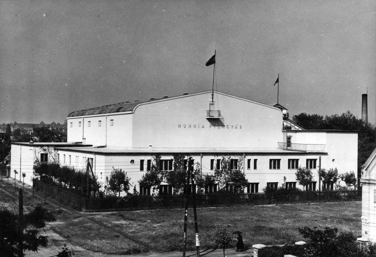 """Az 1936-ban épült ikerműterem, mögötte a Kordáék által 1917-ben létesített üvegfalú """"atelier"""" sarka, amely ma is a gyártelep kellős közepén áll. Az épület Róna utcai homlokzatának jobb szélén van ma a főbejárat, akkor a Bácskai utcából egy elegáns kapun át lehetett bejutni az udvarra, s a betérőt a kapu oszlopainak tetején egy-egy kő holló emlékeztette az egykori Corvin filmgyárra."""