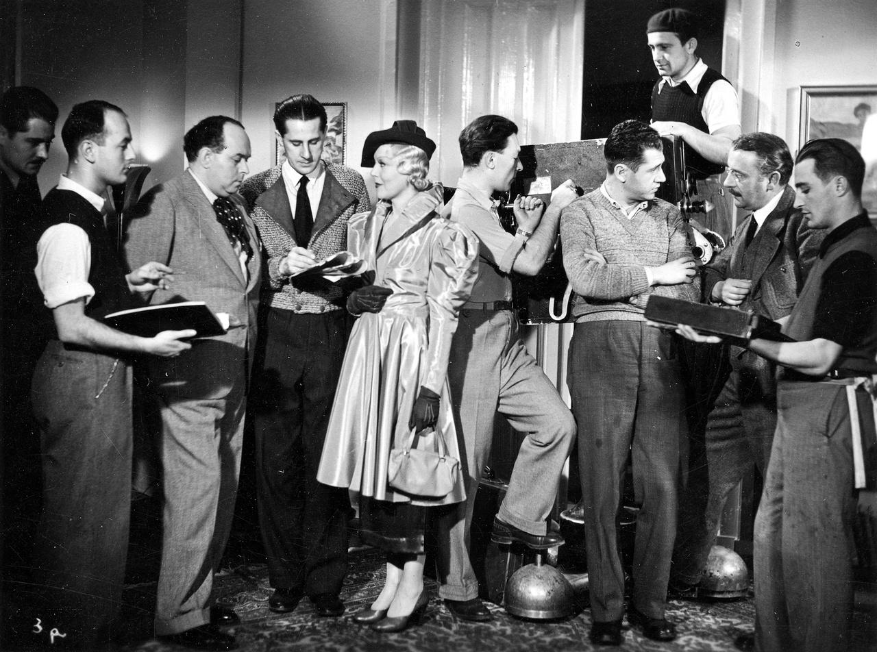 Felvételi szünet az 1935-ös Okos mama forgatásán. A kép közepén álló címszereplő Kosáry Emmy éppen Kabos Gyulával beszélget. Közöttük a korszak befutott rendezője, Martonffy Emil, aki kezében a forgatókönyvvel, bizonyára éppen átír valamit a soron következő jelenet szövegén.
