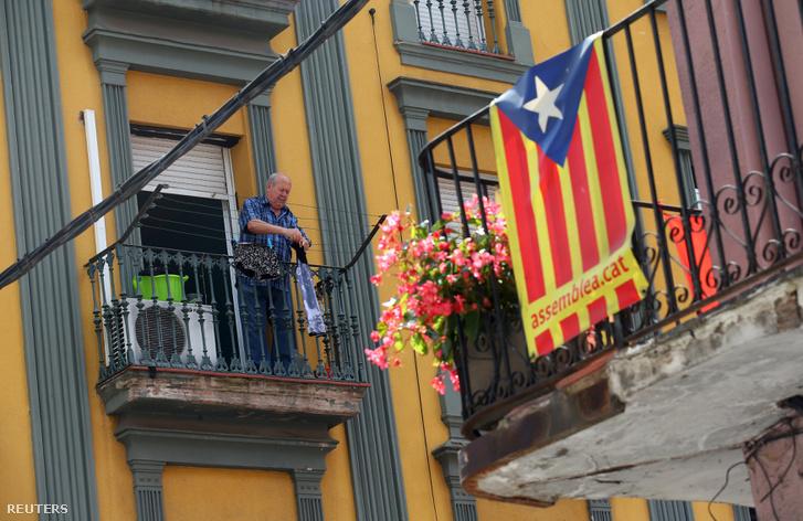 Egy férfi tereget Ripollban, mellette a katalánok nemzeti zászlaja, az Estelada van kifüggesztve