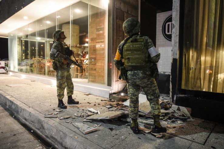 Két katona egy sérült épület előtt.