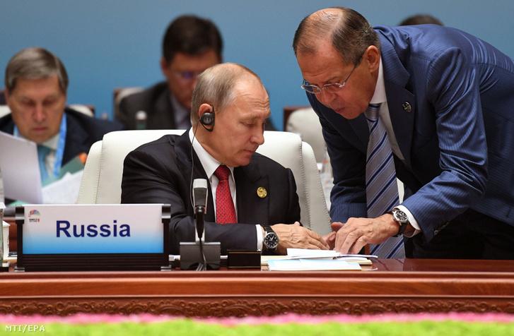 Vlagyimir Putyin orosz elnök (b) és Szergej Lavrov orosz külügyminiszter egy iratot néz a Brazíliát, Oroszországot, Indiát, Kínát és Dél-Afrikát tömörítő BRICS-országok csúcstalálkozóján