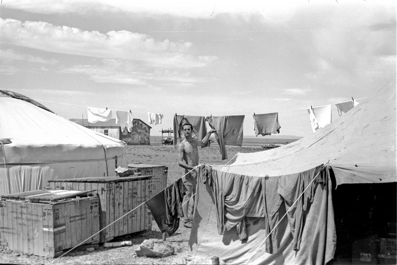 """Expedíciós tábor a sivatagban, a képen Király Ernő tereget. A magyar kutatók egyik bázisa az Ulánbátortól 500 kilométerre délre lévő Dalanzagdad közelében volt. Igaz, a távolság relatív, ők kéthetente tudtak bemenni ide egyszer, hogy feltöltsék a készleteiket. Repülővel persze mindenhová el lehet jutni: amikor egy alkalommal a fővárosból repültek ide, egy helyi utasnak eszébe jutott, hogy - itt most újra Bagi Róbertnek adjuk át a szót -  """"útközben le kellene szállnia, mert van ott neki egy lakat, amit még nem kapott meg a sógorától. Volt nála egy üveg ital, azt odaadta a pilótának, az meg kinézett egy helyet a sivatagban, és letette a gépet. A fickó elment a jurtába, adott két pofont a sógorának, visszakapta a lakatot, és már mentünk is tovább."""""""