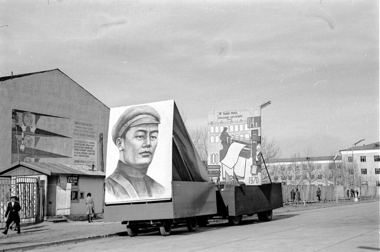 """Szühebátor, az 1921-es mongol forradalom vezéralakjának a képe, valamint """"A 4. ötéves terv kiadványai"""" beszerzésére buzdító felirat. Mongólia a polgárháborús állapotba zuhanó Kínától a huszas években nyerte el bolsevik segítséggel a függetlenségét, a Szovjetunió után ők lettek a világ második szocialista állama. A fotó az ugyancsak Szühebátorról elnevezett nyomda előtt készült. Bár az egykor szintén az ő nevét viselő ulánbátori főteret a rendszerváltás után átkeresztelték Dzsingisz kánra, a szocialista államalapító téren álló szobrát nem bántották, az áll ma is, ahogy a kultusza sem enyészett el a kurzusváltás ellenére sem."""