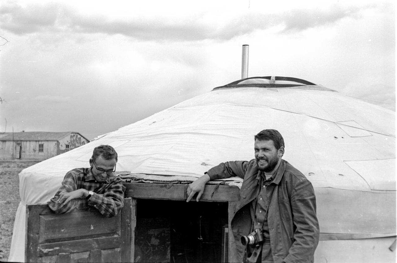 """Két magyar kutató, Taba Sándor és Rezessy Géza az """"irodajurta"""" előtt, középen a konvektor kéménye. Bár itt lengébb az öltözék, telente nem ritka a mínusz 30 fokos hideg sem a sivatagban, a hőmérsékletet a magyar kutatók viccesen csak úgy lőtték be egymás között, hogy hány """"tabagatyányi"""" hideg van. Fogadások Filtol cigibe, próbamérések """"Heiland graviméterrel"""", nyersanyag a fotózáshoz a Bromofort fényképpapír dobozból - pár jurtányi európai sziget Ázsia közepén."""