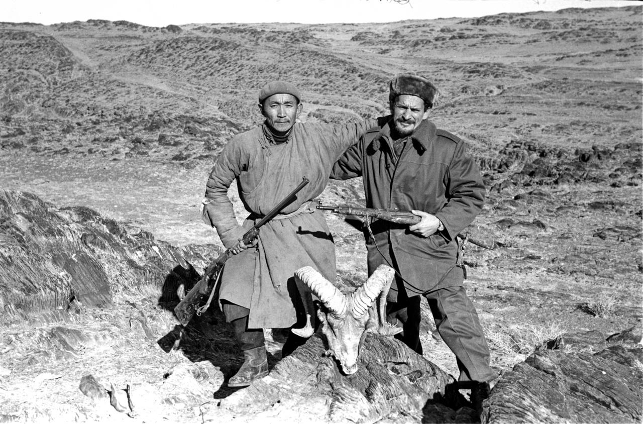 Bagi Róbert (itt a kép jobb oldalán, egy zergefej mögött) a Magyar - Mongol Vízkutató Expedíció tagjaként ment 1969-ben kétéves kiküldetésre a Góbi sivatagba. Bár Magyarországon időnként olyan rémhírek szállingóztak, hogy arrafelé néha csak úgy elássák az embert a sivatagban, ő nem csak egészségesen tért haza, de igen élvezte is a kint létet: ha nem kellett volna külön lennie a feleségétől, maradt volna tovább is szívesen. A tavaly elhunyt mérnök mongóliai fotóiból hat tekercs fekete-fehér negatív és öt tekercs színes dia maradt meg a képek pontos leírásával, ezekből válogattunk.