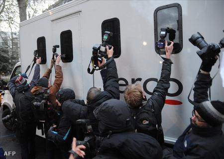 Riporterek fotózni próbálnak a Westminster rendőrbíróság hátsó kapuján át távozó, és feltehetőleg Julian Assange-ot,szállító rabszállító autó ablakain keresztül