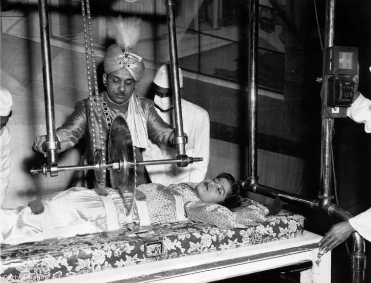 Sorcar, az indiai mágus éppen kettévágja asszisztensét, Dipty Dey-t a londoni Duke of York's színházban, 1956-ban