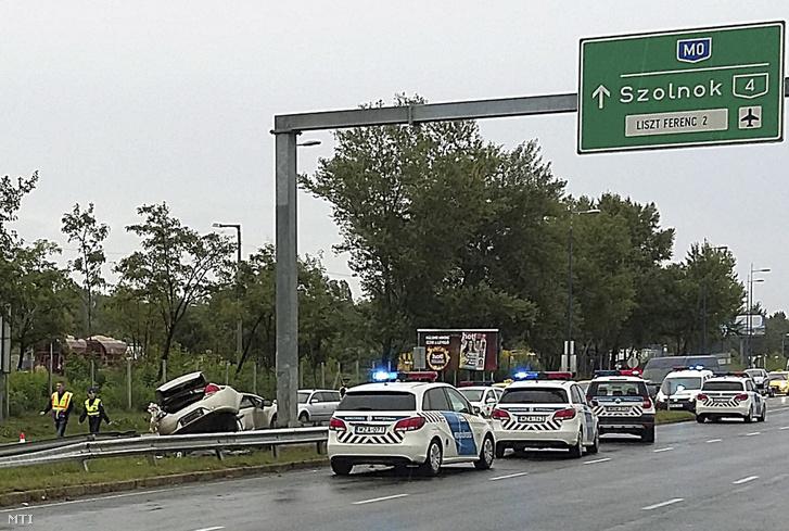 Összeroncsolódott személyautó mellett helyszínelnek rendõrök az Üllői út és a Ferihegyi repülőtérre vezető gyorsforgalmi út kereszteződésének közelében