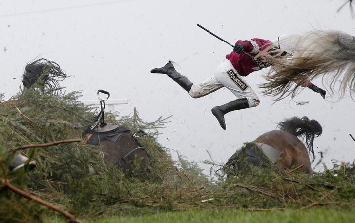 Nina Carberry zsoké leröpül a lováról, Sir Des Champsról (balra), amikor buknak a The Chair elnevezésű akadálynál a legendás Grand National lóversenyen az Aintree versenypályán Liverpool mellett április 9-én. Egy másik ló, On His Own (jobbra) is bukott ennél az akadálynál, másodpercekkel az előtt, hogy Sir Des Champs ugrani készült. Egyik ló és lovas sem sérült meg. (Sport - 1. díj, egyedi)