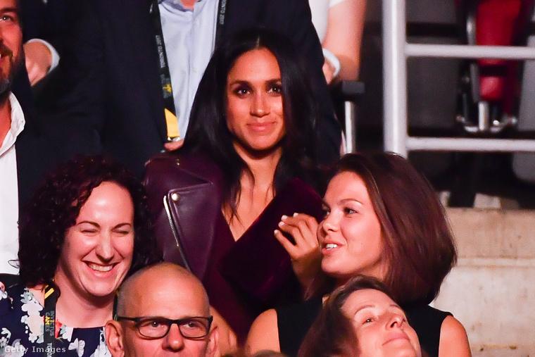...miközben a barátnője, Meghan Markle, pár sorral előttük ült