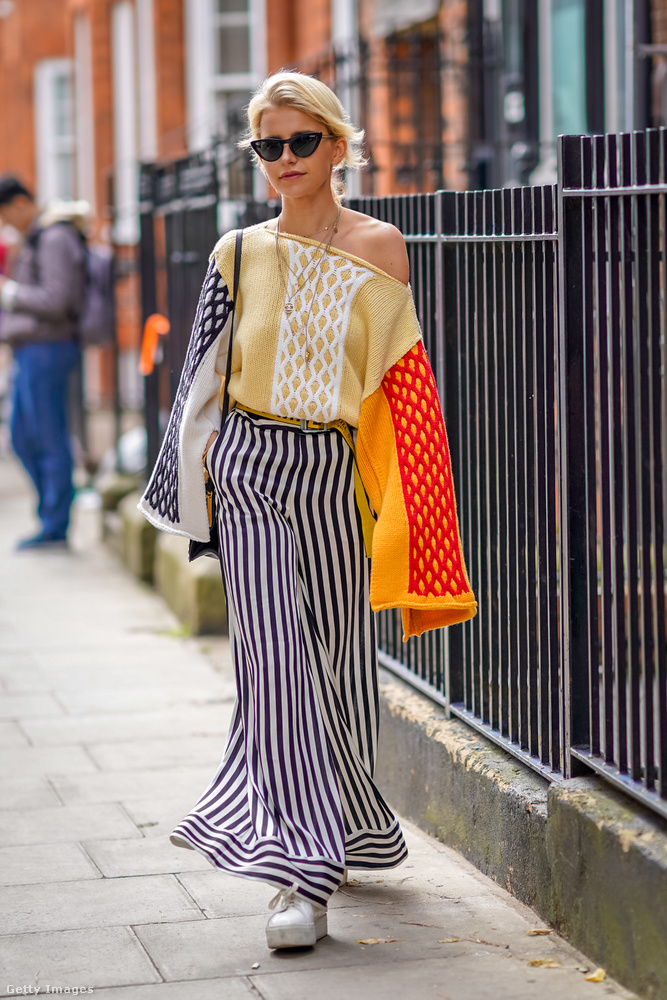 Fehér cipő, csíkos pantalló és színes vállvillantós pulóver Caroline Dauron Londonban.