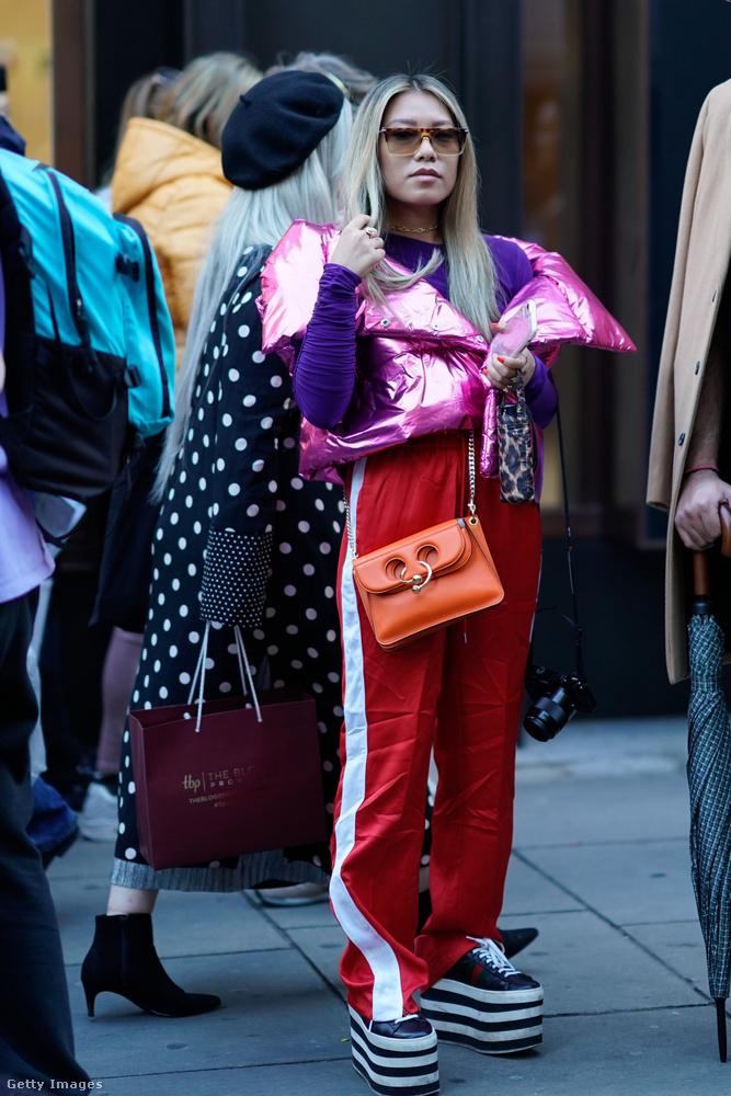 Oldalt csíkos játszósnadrág, pufikabátszerű boleró, narancssárga táska és telitalpú cipő Londonban.