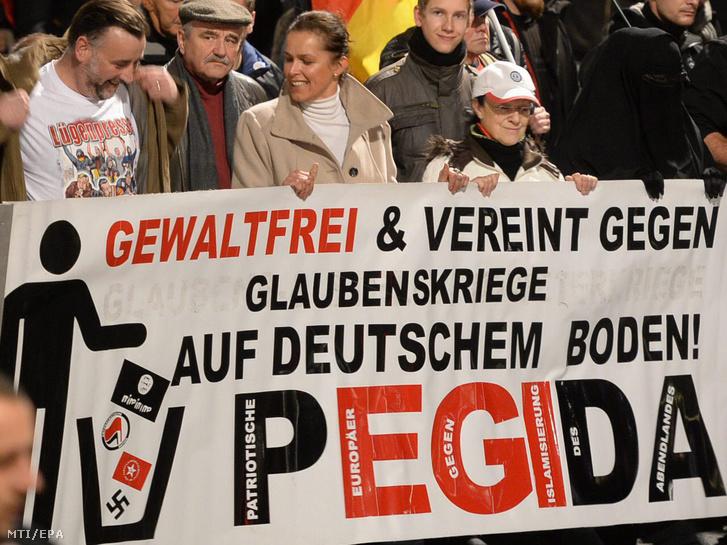 Lutz Bachmann a Hazafias Európaiak a Nyugat Iszlamizálódása Ellen a PEGIDA német mozgalom egyik társalapítója (b) és Tatjana Festerling a menekültellenes Alternatíva Németországnak (AfD) párt volt tagja (k) a PEGIDA drezdai tüntetésén 2015. november 9-én. A transzparensen olvasható felirat jelentése: Erõszakmentesen és együtt a német földön történõ vallásháború ellen!