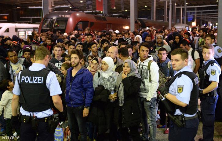 Magyarországról Ausztrián keresztül Németországba érkezett illegális bevándorlók rendőrök felügyeletével várakoznak a müncheni főpályaudvaron 2015. szeptember 12-én