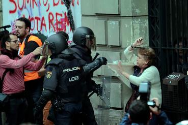 Egy idős nőt húznak ki a tömegből spanyol rohamrendőrök Barcelonában.
