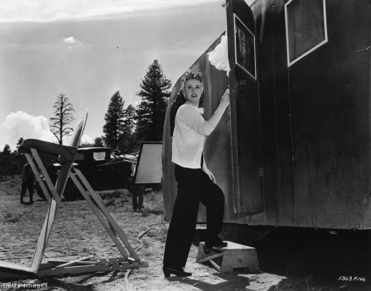 Deanna Durbin belép az öltözőjéül szolgáló vagonba a Universal musicaljének, a 'Can't help Singing'-nek a forgatásán 1944-ben