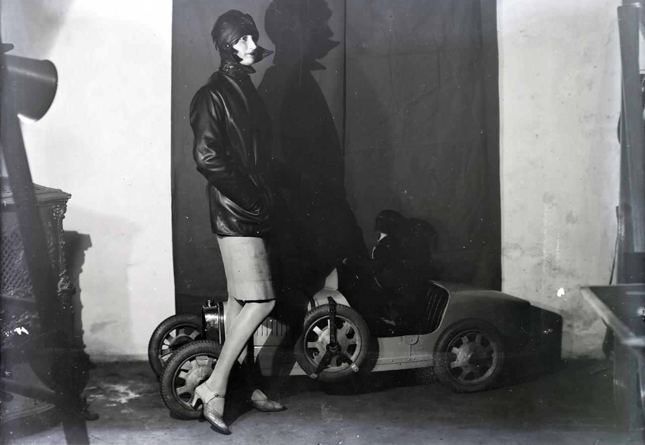 Divatkép a harmincas évekből: porköpeny nőknek, játékautóval és négylábú sofőrrel.