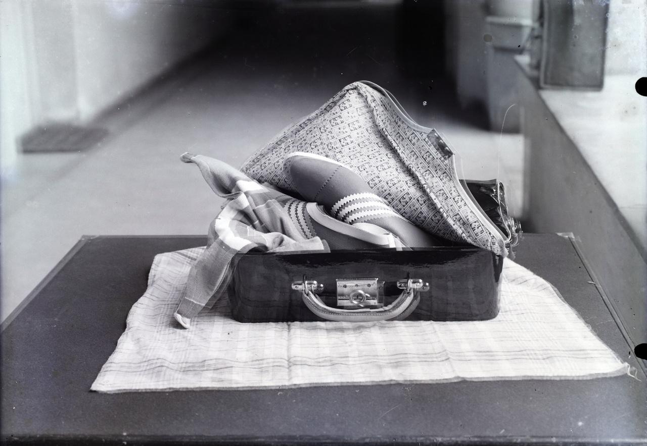 Finom, könnyű szabású sportcipő és tükörfényesre polírozott műbőr bőrönd katalógusfotózása egy budapesti bérház udvarán.