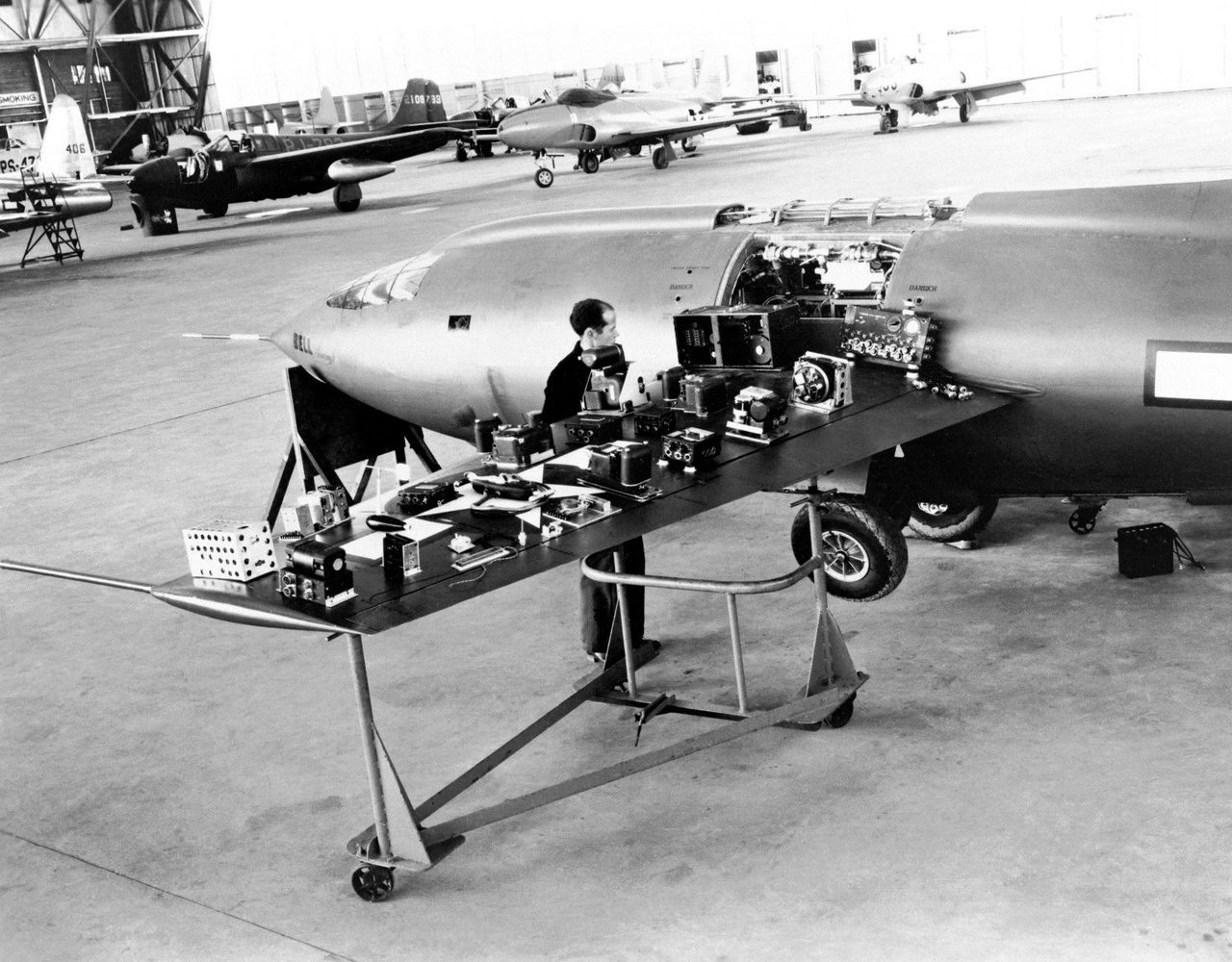 Egy kiállított X-1 az Edwards légibázison tartott nyílt nap alkalmával, 1947-48 környékén. A repülőgép szárnyára kipakolva az X-1-be épített műszerek láthatók, a háttérben sugárhajtású vadászgépek.