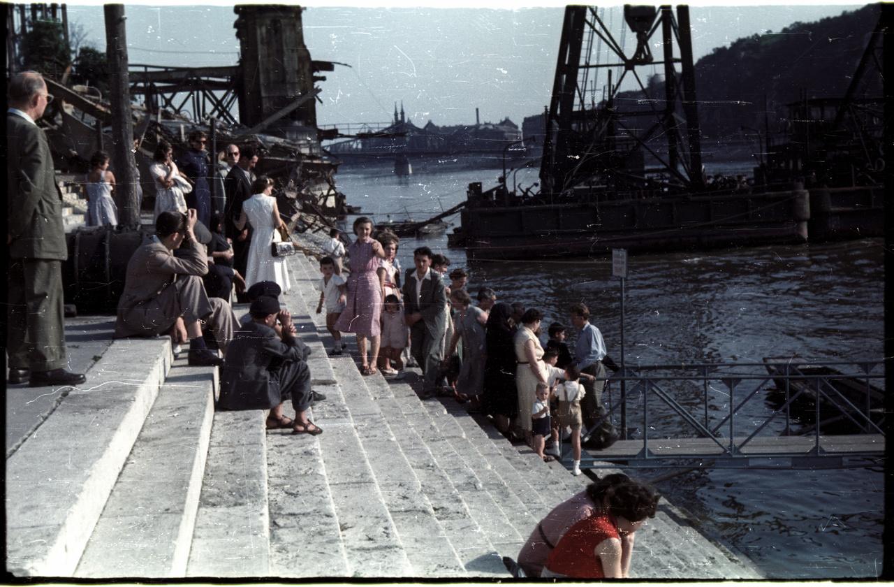 Bontják az Erzsébet híd torzóját, a munkákat a partról figyelik az emberek.