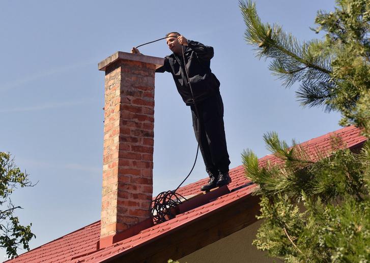 A katasztrófavédelem kéményseprőipari szakembere egy kéményt ellenőriz egy csobánkai családi ház tetjén 2016 július 18-án